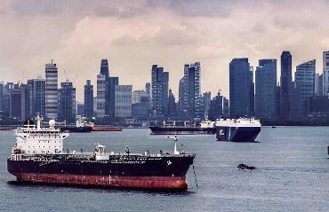 Veduta di skyline di grande città con navi mercantili nel porto