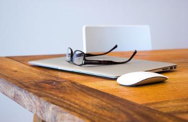 Occhiali da vista poggiati su computer su una scrivania