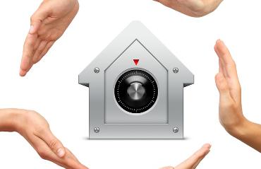 Quattro mani che proteggono una cassaforte a forma di casa