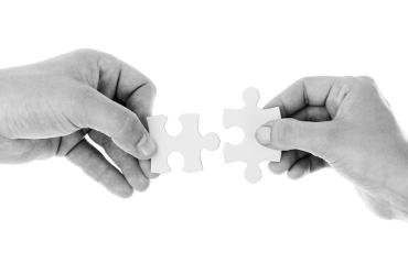 Due mani che uniscono due pezzi di puzzle