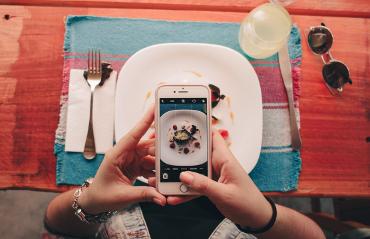 Ragazza che fotografa un piatto con il suo smartphone
