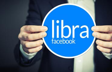 Mani che stringono cerchio con indicazione Libra la criptovaluta di Facebook