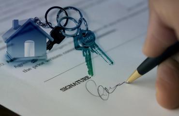 Uomo che firma un contratto immobiliare con accanto portachiavi a forma di casa
